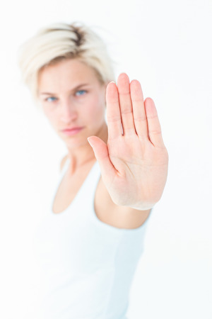 dreariness: Angry pretty blonde showing her hand on white background Stock Photo