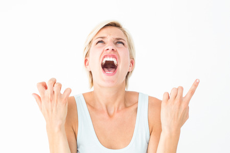 Upset woman screaming with hands up on white background