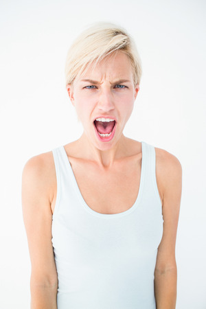 angry blonde: Angry blonde woman screaming on white background Stock Photo