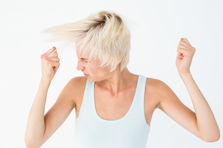 clenching fists: Angry woman shaking her head on white background
