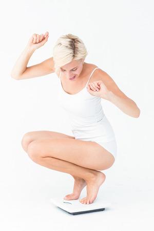 silhouette feminine: Bonne jolie femme accroupie sur une balance sur fond blanc