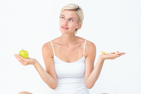 deciding: Pretty woman deciding between pizza and apple on white background Stock Photo