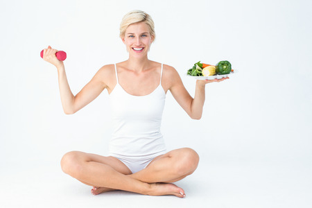 health fair: Attractive woman holding vegetables plate and dumbbell on white background