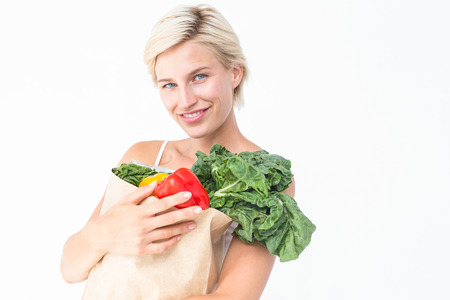 woman holding bag: Attractive woman holding bag of vegetables on white background