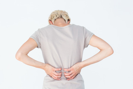 back ache: Blonde woman having a back ache and holding her back on white background