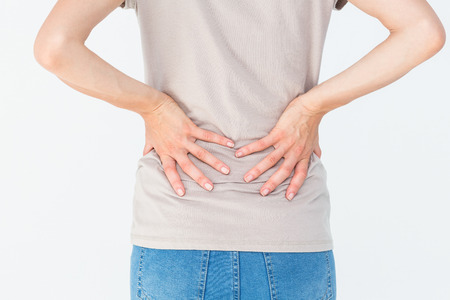 back ache: Woman having a back ache and holding her back on white background