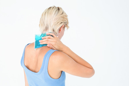 therapy equipment: Blonde woman putting gel pack on neck on white background Stock Photo