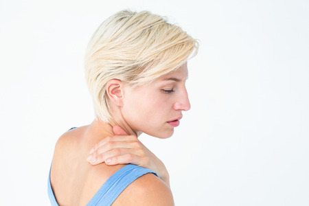 hand rubbing: Casual woman with neck pain on white background