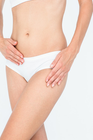 young underwear: Woman touching her belly and hip on white background Stock Photo