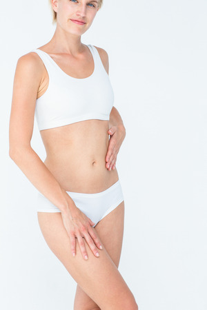body concern: Pretty blonde touching her belly on white background