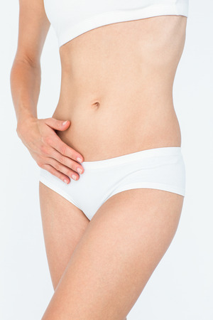 body concern: Woman touching her belly on white background Stock Photo
