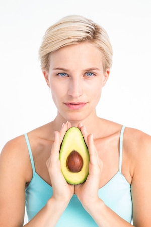 Attractive woman showing half of an avocado on white background photo