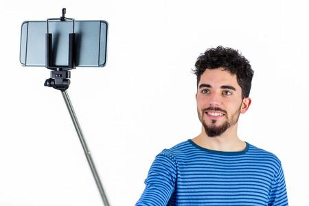 stick: Casual man using a selfie stick shot in studio