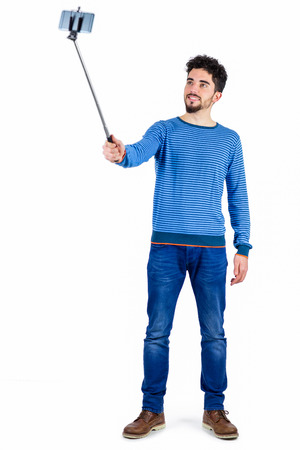 outs: Casual man using a selfie stick shot in studio