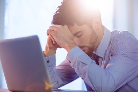 nerveux: Businessman using laptop at desk shot in studio