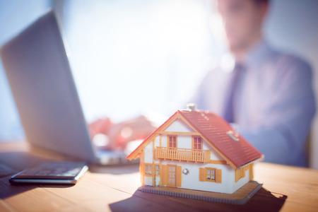 Agencia inmobiliaria utilizando el portátil en el escritorio disparo en estudio Foto de archivo