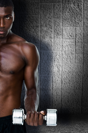 abdominal wall: Serious fit shirtless young man lifting dumbbell against dark grey room Stock Photo