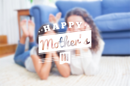 ladies day: mothers day greeting against happy mother and daughter lying on the floor