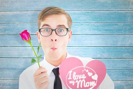 te amo: Inconformista Geeky que sostiene una rosa roja y tarjeta coraz�n contra tablas de madera