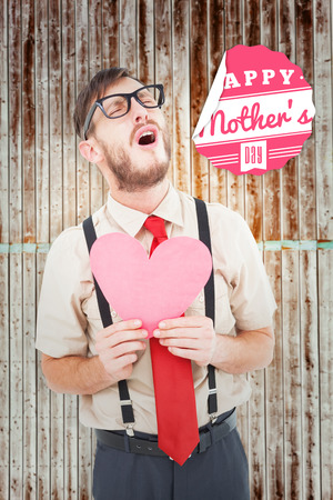 geeky: Geeky hipster crying and holding heart card against wooden planks