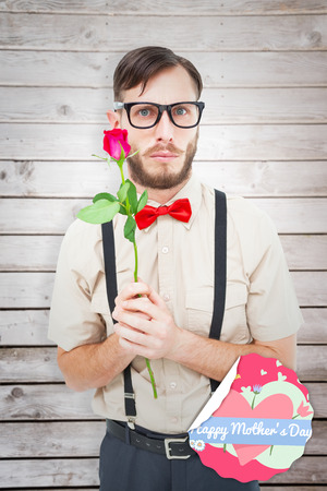 geeky: Geeky hipster offering a rose against wooden planks Stock Photo