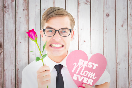 angry computer: Geeky hipster holding a red rose and heart card against wooden planks