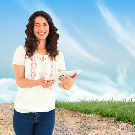 Smiling casual brunette using her tablet pc against road leading out to the horizon photo