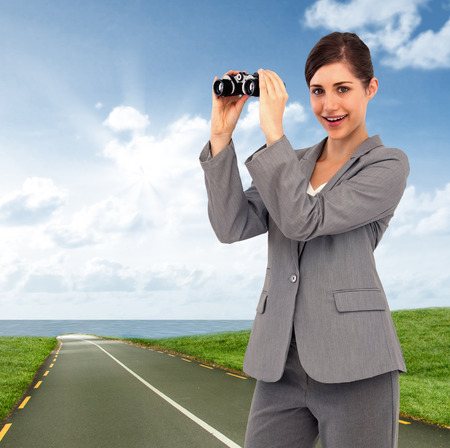 Businesswoman posing with binoculars against road leading out to the horizon photo