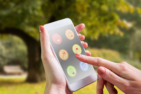 life growth: Hand holding smartphone against trees and meadow in the park Stock Photo