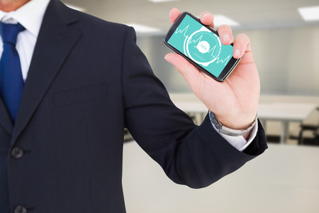 Mid section of a businessman typing on his phone against empty class room photo