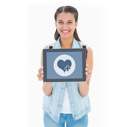 Pretty student showing her tablet pc against heart photo