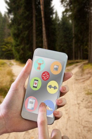 Hand holding smartphone against narrow dirt road leading to two different track along trees photo
