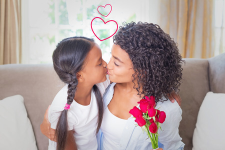girls kissing girls: Heart against pretty mother sitting on the couch kissing her daughter holding roses