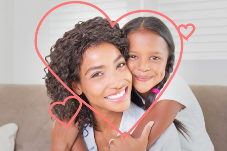 heart against pretty mother sitting on the couch with her daughter smiling at camera photo