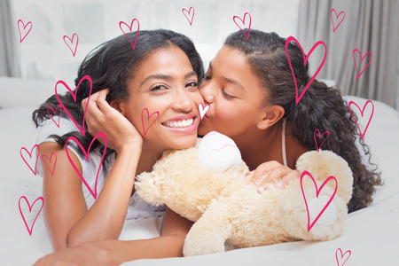 Pretty woman lying on bed with her daughter kissing cheek against red hearts photo