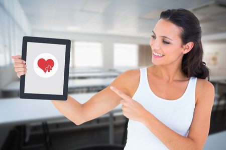 class room: Pretty brunette using tablet pc against empty class room