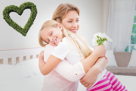 green day: Heart made of leaves against mother and daughter hugging with flowers