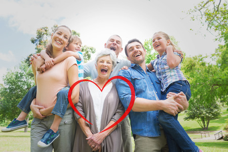 Portrait of cheerful extended family at park against heart