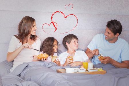 comiendo cereal: Familia que desayuna en la cama contra el corazón
