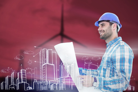 Smiling engineer looking away while holding blueprint against windmill spinning over a green field photo