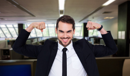 Happy businessman in suit cheering  against empty office with separate units photo