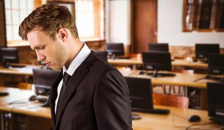 desolaci�n: Apuesto hombre de negocios joven que mira abajo contra la sala de ordenadores