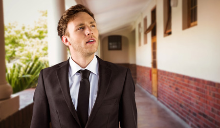 man looking up: Young businessman thinking and looking up against hallway