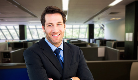 Smiling businessman with arms crossed against empty office with separate units photo