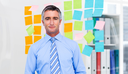 sticky hands: Smiling businessman in suit with hands in pocket posing against closeup of colorful sticky notes at office