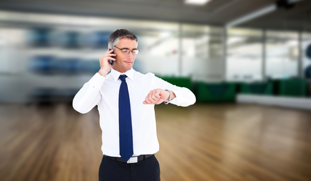 wrist watch: Businessman on the phone looking at his wrist watch against fitness studio