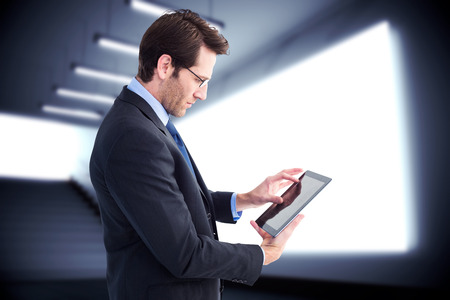 scrolling: Businessman standing while using a tablet pc against grey room