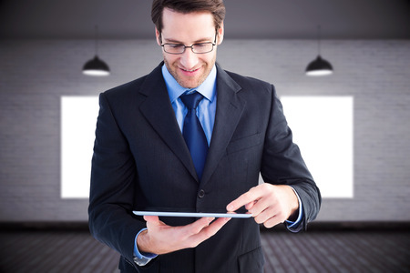 Businessman standing while using a tablet pc against grey room photo