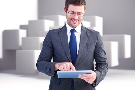 Businessman using his tablet pc  against abstract background photo