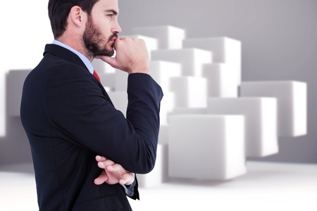 chin: Thinking businessman standing with hand on chin against abstract background Stock Photo